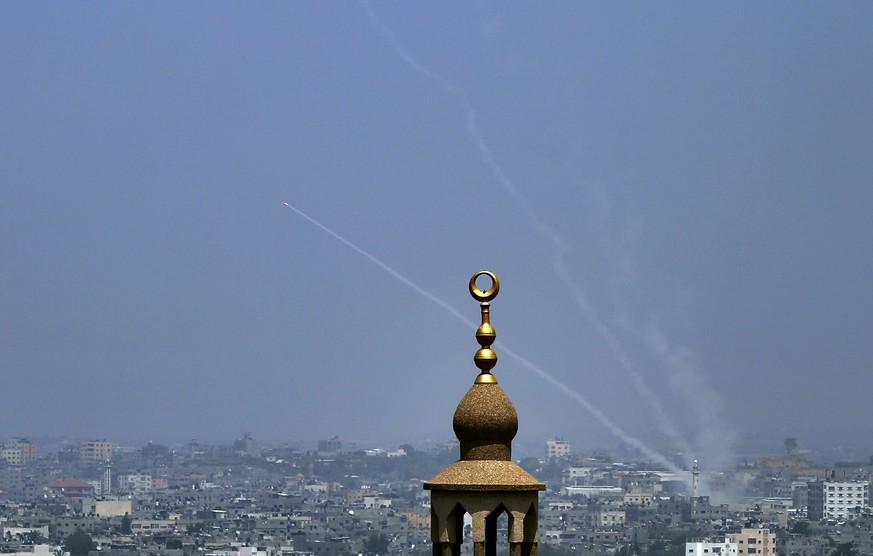Smoke trails are seen as rockets are launched from the Gaza Strip towards Israel, in Gaza City, Saturday, July 14, 2018. The Israeli military carried out its largest daytime airstrike campaign in Gaza since the 2014 war Saturday as Hamas militants fired dozens of rockets into Israel, threatening to spark a wider conflagration after weeks of tensions along the volatile border. (AP Photo/Sami Shehada)