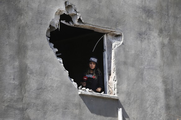 A journalist looks out of an hole on a house that was damaged by a mortar fired from inside Syria, on the Turkish town of Akcakale, southeaster, Turkey, Saturday, Oct. 12, 2019.Nobody got hurt by the attack. The owners of the house weren't home at the time of the attack. Turkey says its military offensive has taken central Ras al-Ayn, a key border town in northeastern Syria, and its most significant gain since its cross-border operation began against Syrian Kurdish fighters began. (AP Photo/Lefteris Pitarakis)