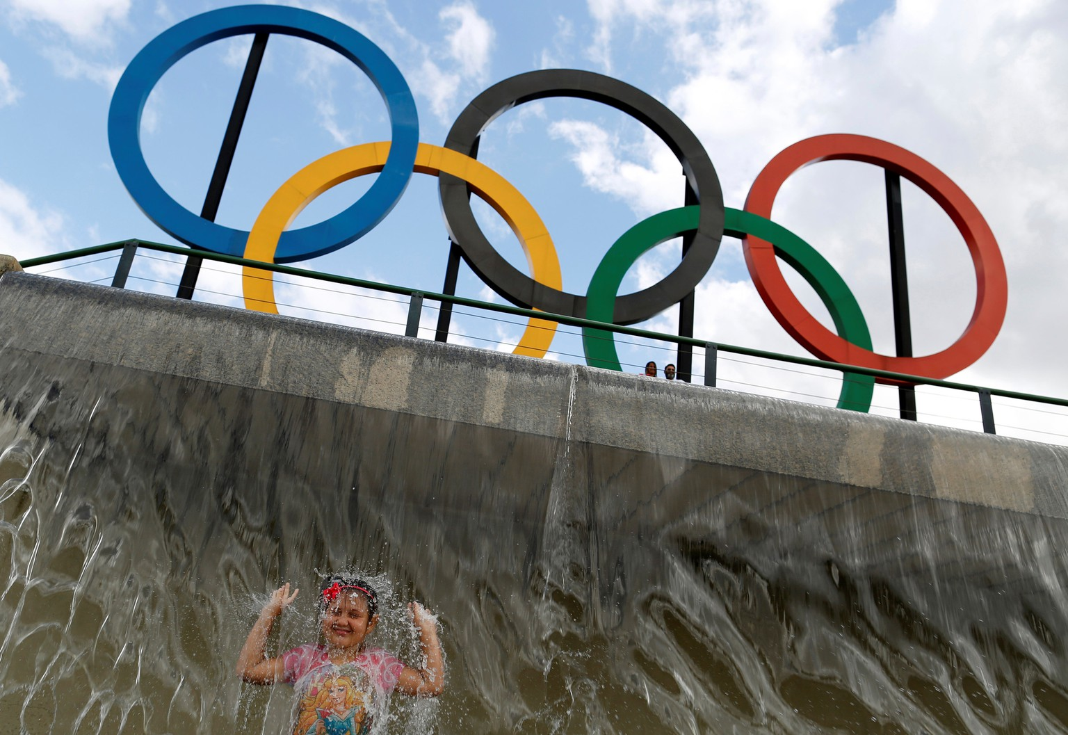 A child plays in water near Olympic rings placed at Madureira Park ahead of the Rio 2016 Olympic Games in Rio de Janeiro, Brazil, July 17, 2016. REUTERS/Bruno Kelly