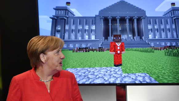 German chancellor Angela Merkel standing beside a Minecraft game, showing her in front of the German Reichstag, during the Gamescom fair for computer games in Cologne, Germany, Tuesday, Aug. 22, 2017. The leading European trade fair for digital gaming culture is the meeting point for global companies from the entertainment industry and the international gaming community. (AP Photo/Martin Meissner)