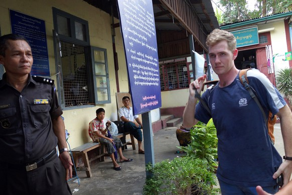 A Myanmar Immigration officer stands as Angus Roberts Watson, an Australian video journalist, leaves the district office of Myanmar Immigration and Population Ministry Thursday, May 8, 2014, in Yangon, Myanmar. Authorities in Myanmar said Thursday they have deported an Australian video journalist for covering a press freedom rally without a proper visa. Agnus Watson, an intern with the Democratic Voice of Burma, boarded a flight Thursday for Thailand. (AP Photo/Khin Maung Win)