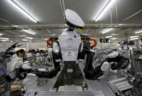 A humanoid robot works side by side with employees in the assembly line at a factory of Glory Ltd., a manufacturer of automatic change dispensers, in Kazo, north of Tokyo, Japan, July 1, 2015. Japanese firms are ramping up spending on robotics and automation, responding at last to premier Shinzo Abe's efforts to stimulate the economy and end two decades of stagnation and deflation. Picture taken July 1, 2015. REUTERS/Issei Kato      TPX IMAGES OF THE DAY
