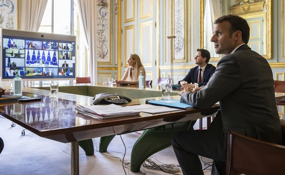 epa08379772 French President Emmanuel Macron (R) attends a video conference call with members of the European Council at the Elysee Palace in Paris, France, 23 April 2020. Countries around the world are taking increased measures to stem the widespread of the SARS-CoV-2 coronavirus which causes the COVID-19 disease.  EPA/IAN LANGSDON / POOL