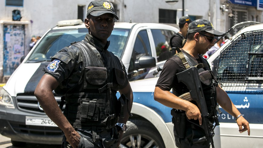 Tunisian police officers stand guard after an explosion in Tunis, Thursday June 27, 2019. Twin suicide attacks targeting security forces struck Tunisia's capital on Thursday, killing at least one patrol officer and injuring at least eight people. (AP Photo/Riadh Dridi)