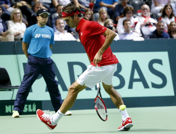 Switzerland's Roger Federer returns the ball between his legs during his Davis Cup World Group play-off tennis match against Jesse Huta Galung of the Netherlands at the Palexpo Arena in Geneva September 18, 2015.  REUTERS/Denis Balibouse