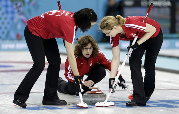 Switzerland's skip Mirjam Ott, center, delivers the rock while teammates Carmen Kueng, left, and Janine Greiner, right, sweep the ice during the women's curling competition at the 2014 Winter Olympics, Tuesday, Feb. 11, 2014, in Sochi, Russia. (AP Photo/Wong Maye-E)