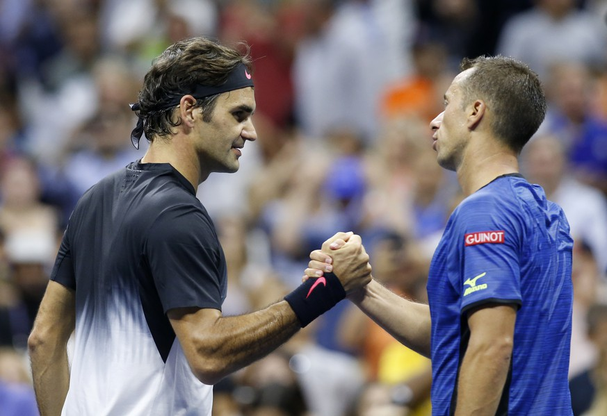 Roger Federer, left, of Switzerland, greets Philipp Kohlschreiber, of Germany, at the net after defeating Kohlschreiber, 6-4, 6-2, 7-5, in a fourth-round match at the U.S. Open tennis tournament in New York, Monday, Sept. 4, 2017. (AP Photo/Kathy Willens)
