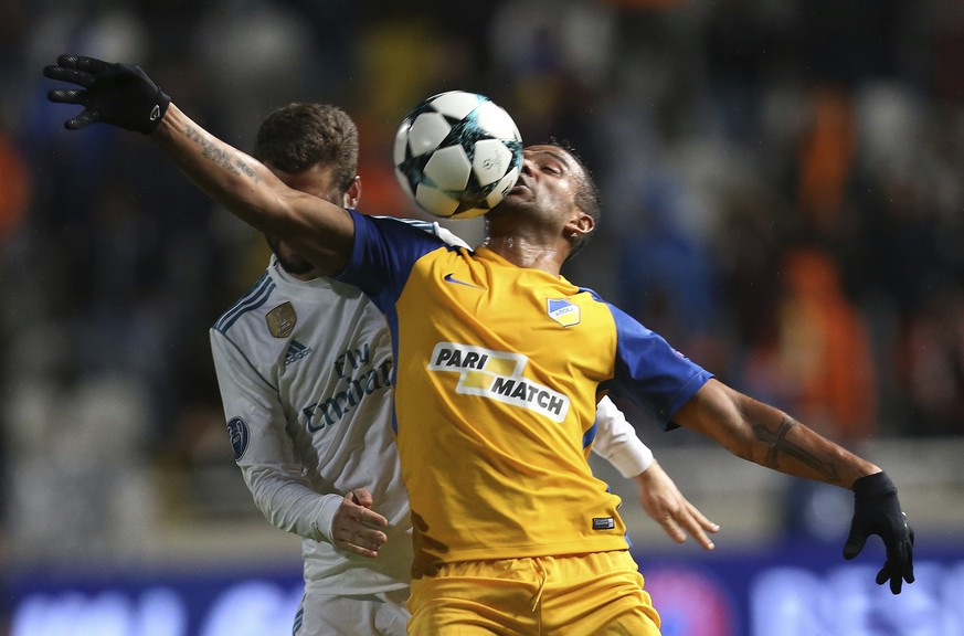 APOEL's Lorenzo Ebecilio, right, and Real Madrid's Nacho challenge for the ball during the Champions League Group H soccer match between APOEL Nicosia and Real Madrid at GSP stadium, in Nicosia, on Tuesday, Nov. 21, 2017. Real Madrid won 6-0. (AP Photo/Petros Karadjias)