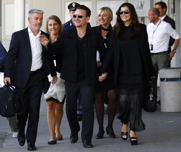 Irish singer Bono, lead singer of group U2, and his wife Ali Hewson arrive to take a taxi boat transporting guests for the wedding of U.S. actor George Clooney and his fiancee Amal Alamuddin, in Venice September 27, 2014. REUTERS/Stefano Rellandini ( ITALY - Tags: ENTERTAINMENT)