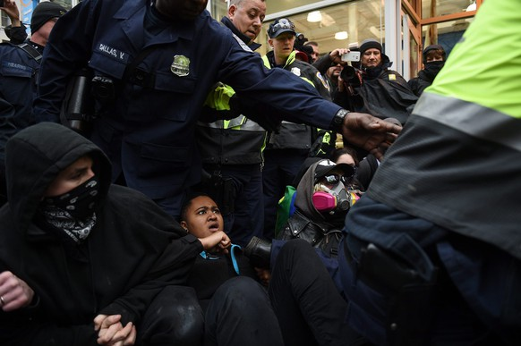 epa05734769 Police step over demonstrators who block one of the entrances to the route of the inauguration parade at 10th Street near Pennsylvania Avenue to protest Donald J. Trump who will take the oath of office as he is sworn in as the 45th President of the United States in Washington, DC, USA, 20 January 2017. Trump won the 08 November 2016 election to become the next US President.  EPA/Astrid Riecken
