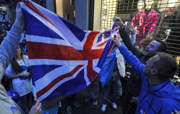 Pro-Independence supporters attempt to burn to a Union Flag in George Square, Glasgow, Scotland, on September 18, 2014, during a referendum on Scottish independence. Scotland began voting Thursday on whether to become independent from Britain in a referendum which has electrified the nation, dominating debate in homes and pubs from Edinburgh to the Highlands. AFP PHOTO / ANDY BUCHANAN