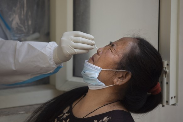 A health worker takes a nasal swab sample at a COVID-19 testing center in New Delhi, India, Thursday, Oct. 29, 2020. India's confirmed coronavirus caseload surpassed 8 million on Thursday with daily infections dipping to the lowest level this week, as concerns grew over a major Hindu festival season and winter setting in. (AP Photo/Altaf Qadri)
