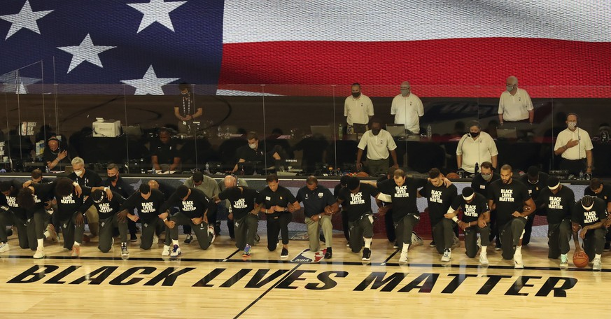 Players and coaches kneel during the national anthem before the Utah Jazz against the New Orleans Pelicans NBA basketball game Thursday, July 30, 2020, in Lake Buena Vista, Fla. (Charles King/Orlando Sentinel via AP)
