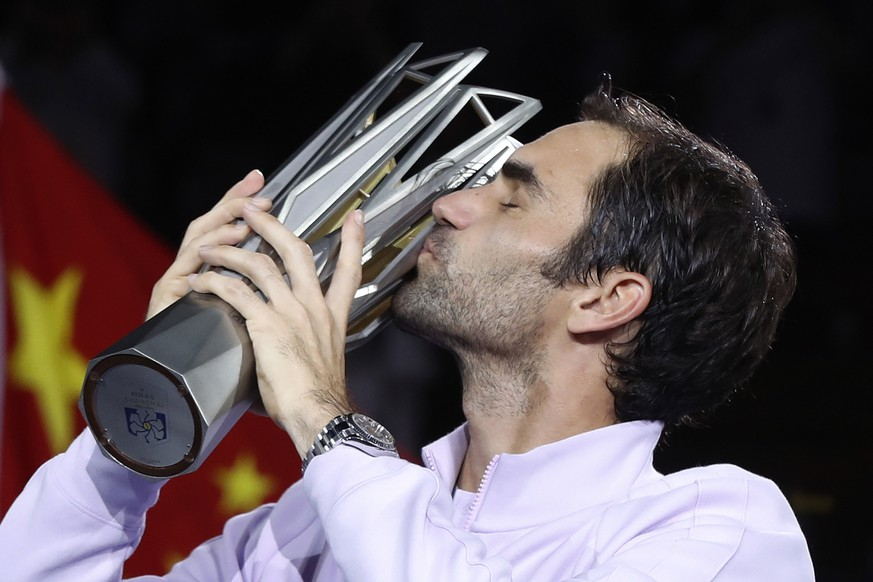 Roger Federer of Switzerland kisses his trophy after defeating Rafael Nadal of Spain in their men's singles final match to win the Shanghai Masters tennis tournament at Qizhong Forest Sports City Tennis Center in Shanghai, China, Sunday, Oct. 15, 2017. (AP Photo/Andy Wong)