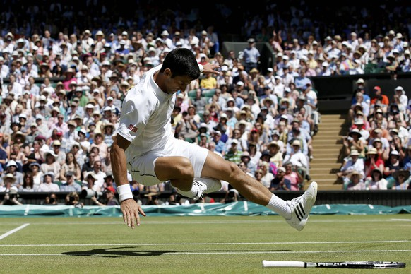 Novak Djokovic of Serbia falls over during his match against Richard Gasquet of France at the Wimbledon Tennis Championships in London, July 10, 2015.                                      REUTERS/Adrian Dennis/Pool