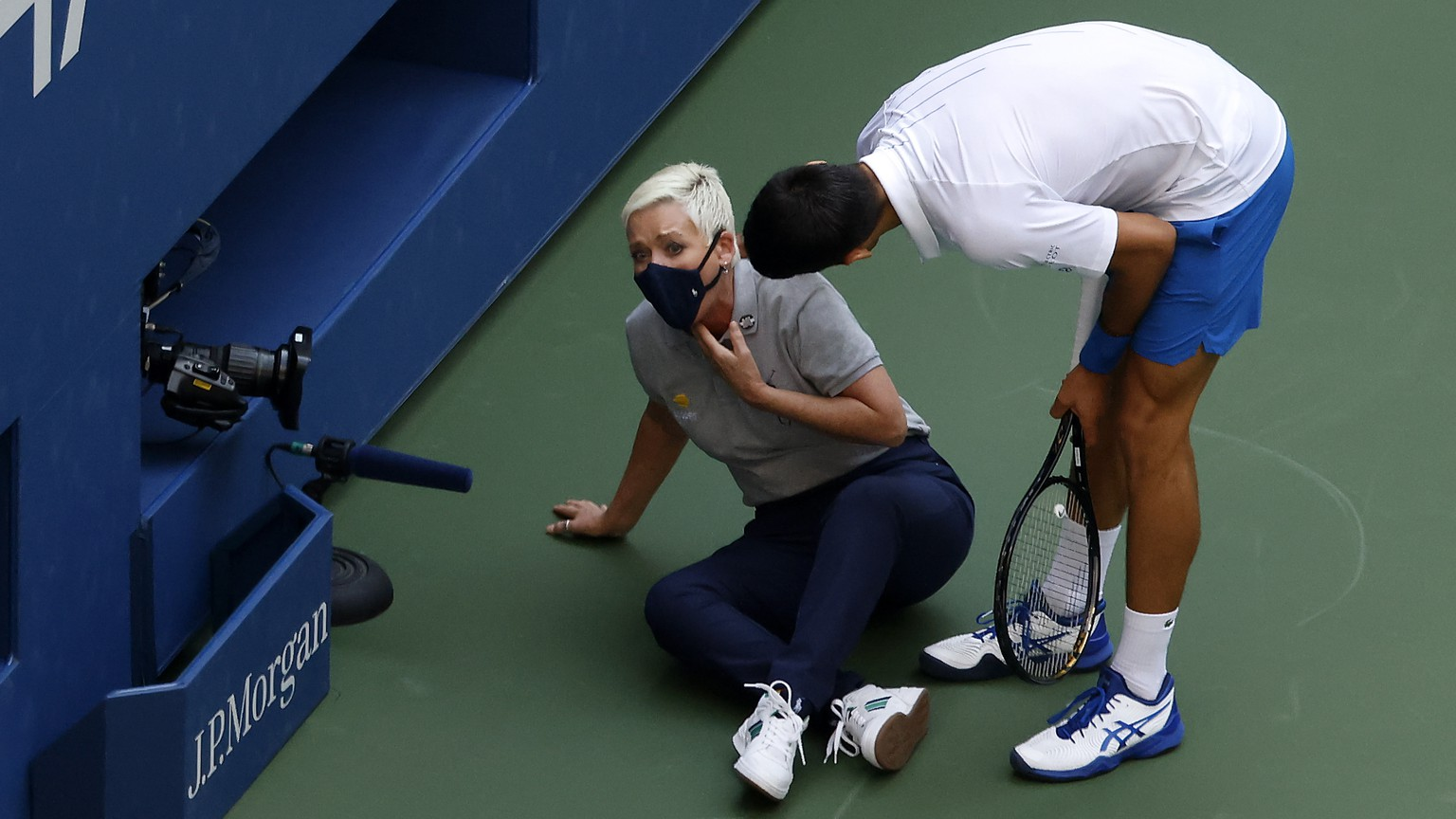 epa08651641 Novak Djokovic of Serbia (R) tries to help a linesperson after hitting her with a ball in the throat during his match against Pablo Carreno Busta of Spain on the seventh day of the US Open Tennis Championships at the USTA National Tennis Center in Flushing Meadows, New York, USA, 06 September 2020. Djokovic was defaulted from tournament. Due to the coronavirus pandemic, the US Open is being played without fans and runs from 31 August through 13 September.  EPA/JASON SZENES