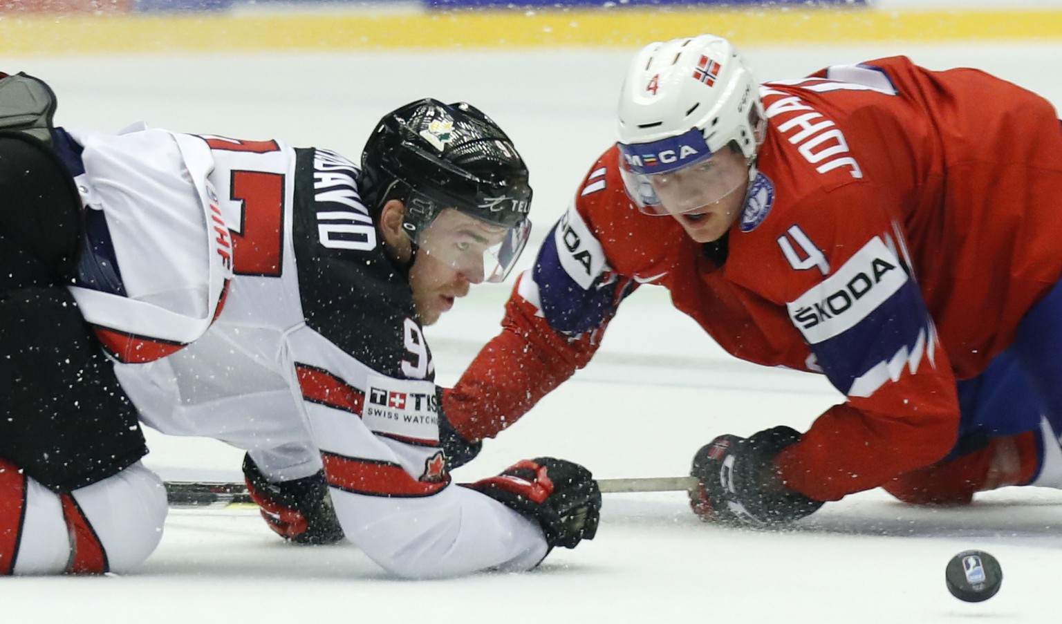 Canada's Connor McDavid, left, challenges for the puck with Norway's Johannes Johannesen, right, during the Ice Hockey World Championships group B match between Norway and Canada at the Jyske Bank Boxen arena in Herning, Denmark, Thursday, May 10, 2018. (AP Photo/Petr David Josek)