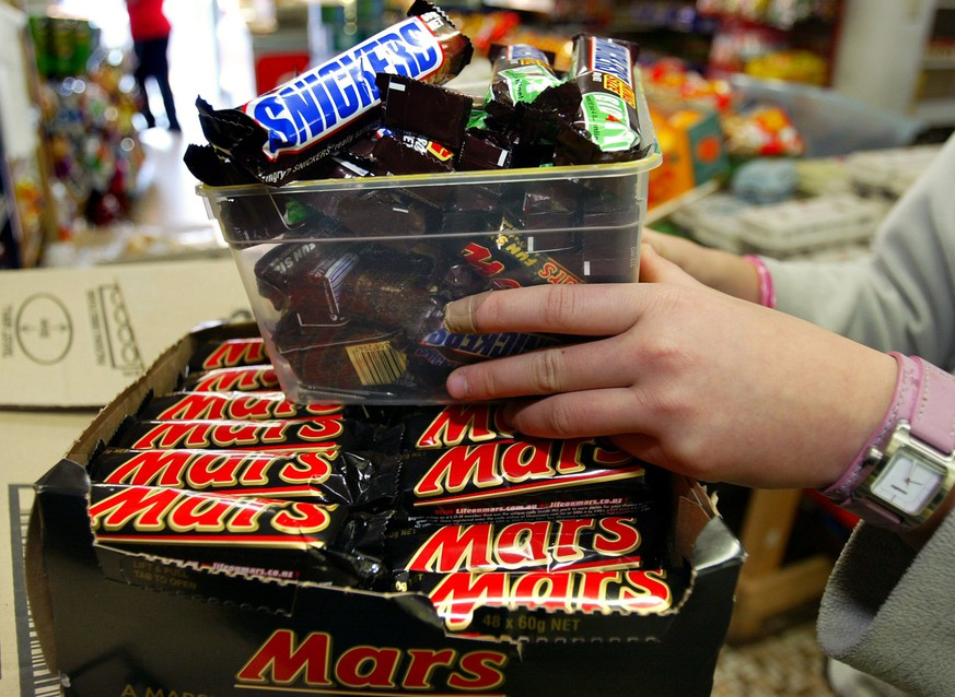 A shopkeeper in removes Mars Bars and Snickers Bars from the shelves of her convenience store in this picture taken on July 2, 2005 in Sydney, Australia. U.S. chocolate maker Mars Inc announced February 23, 2016 a recall of Mars and Snickers bars as well as some other products in Germany on Tuesday after bits of plastic were found in one of its products.  Picture taken July 2, 2005.    REUTERS/Will Burgess/Files
