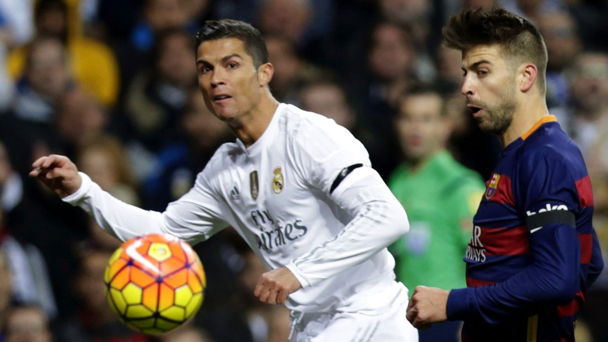 epa05036222 Real Madrid's Portuguese striker Cristiano Ronaldo (L) duels for the ball with FC Barcelona's defender Gerard Pique (R) during the Spanish Liga Primera Division soccer match played at Santiago Bernabeu stadium in Madrid, Spain, 21 November 2015.  EPA/Javier Lizon