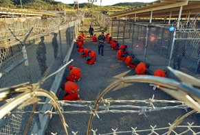 [THEMA - ZUM JAHRESTAG DER ALLGEMEINEN ERKLAERUNG DER MENSCHENRECHTE VOM 10. DEZEMBER - ARTIKEL 9: Niemand darf willkuerlich festgenommen, in Haft gehalten oder des Landes verwiesen werden.] -  this photo released January 18, 2002 by the Department of Defense, Al-Qaeda and Taliban detainees in orange jumpsuits sit in a holding area under the surveillence of US military police at Camp X-Ray at Naval Base Guantanamo Bay, Cuba, during in-processing to the temporary detention facility 11 January 2002.  The detainees, captured in Afghanistan during Operation Enduring Freedom, are given a basic physical exam by a doctor, to include a chest x-ray blood samples drawn to assess their health.  (KEYSTONE/EPA PHOTO/AFP/DOD/US NAVY/Shane T. McCoy)