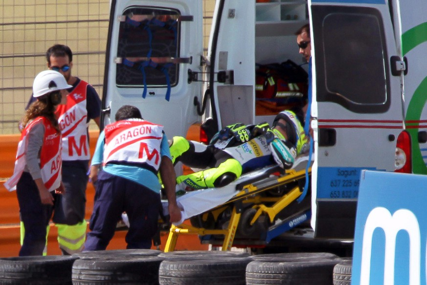 epa04952252 Swiss Moto2 rider Dominique Aegerter (C) of the Technomag Racing Interwetten team is taken into an ambulance after crashing during the Moto2 race of the Motorcycling Grand Prix of Aragon at Motorland circuit in Alcaniz, Spain, 27 September 2015.  EPA/ANTONIO GARCIA