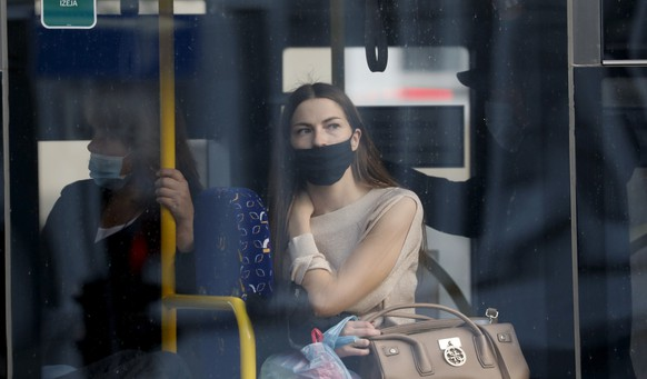 epa08727229 People wearing protective face masks in a trolleybus in Riga, Latvia, 07 October Face masks use is mandatory in public transport from 07 October in Latvia.  EPA/TOMS KALNINS