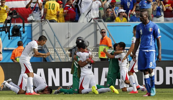 Italy's Mario Balotelli, right, walks away as Costa Rican players celebrate after the group D World Cup soccer match between Italy and Costa Rica at the Arena Pernambuco in Recife, Brazil, Friday, June 20, 2014. Costa Rica won the match 1-0. (AP Photo/Frank Augstein)