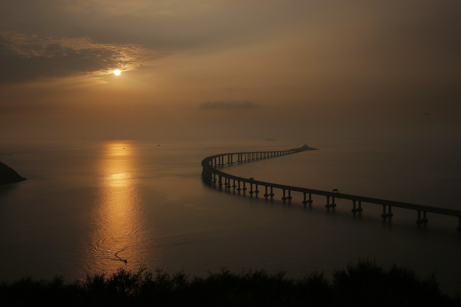 The Hong Kong-Zhuhai-Macau Bridge is seen against the sunset in Hong Kong, Monday, Oct. 22, 2018. The bridge, the world's longest cross-sea project, which has a total length of 55 kilometers (34 miles), will have opening ceremony in Zhuhai on Oct. 23. (AP Photo/Kin Cheung)