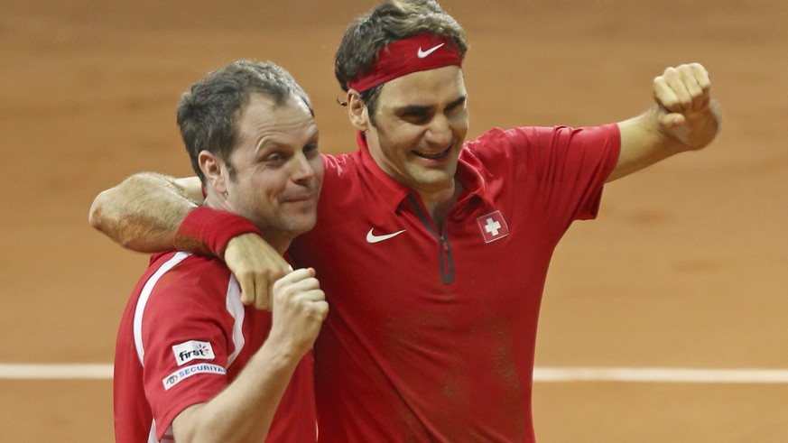 Swiss coach Severin Luthi, left, and Switzerland's Roger Federer celebrate after Federer defeated France's Richard Gasquet in the Davis Cup final between France and Switzerland at Stade Pierre Mauroy in Lille, northern France, Sunday, Nov. 23, 2014. (AP Photo/Peter Dejong)
