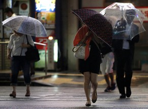 People holding umbrellas cross a street in Tokyo during rain and winds caused by tropical storm Neoguri as the storm approaches Tokyo, July 10, 2014. Heavy rain battered a wide swathe of Japan on Thursday, sending rivers over their banks and setting off a landslide as a weakened but still dangerous storm made landfall and headed east, leaving three people dead. REUTERS/Yuya Shino (JAPAN - Tags: ENVIRONMENT DISASTER)