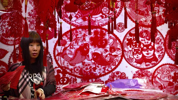 A vendor selling Lunar New Year decorations waits for customers at a wholesale market in Beijing, Tuesday, Feb. 13, 2018. Chinese worldwide are preparing to celebrate the Lunar New Year on Feb. 16 with family reunions, firecrackers, and traditional food as they welcome the Year of the Dog. (AP Photo/Mark Schiefelbein)