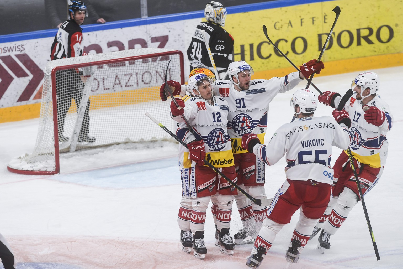 Laker's player Steve Moses, center, celebrates with his teammates the 1-2 goal against Lugano's goalkeeper  Niklas Schlegel, during the fifth leg of the playoff best of seven match of the Swiss National League between HC Lugano and SC Rapperswil-Jona Lakers, at the ice stadium Corner Arena in Lugano, on Wednesday, 21 April 2021. (KEYSTONE/Ti-Press/Alessandro Crinari)
