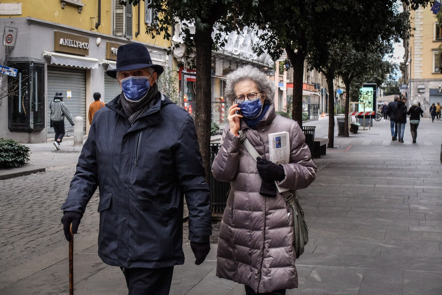 epa08249348 Two passers-by wear a protective face mask as they walk in Milan, Italy, 26 February 2020. Civil Protection Chief Angelo Borrelli said that the number of people which have died due to the COVID19 coronavirus in Italy has climbed to 12 while 374 have contracted the virus.  EPA/MATTEO CORNER