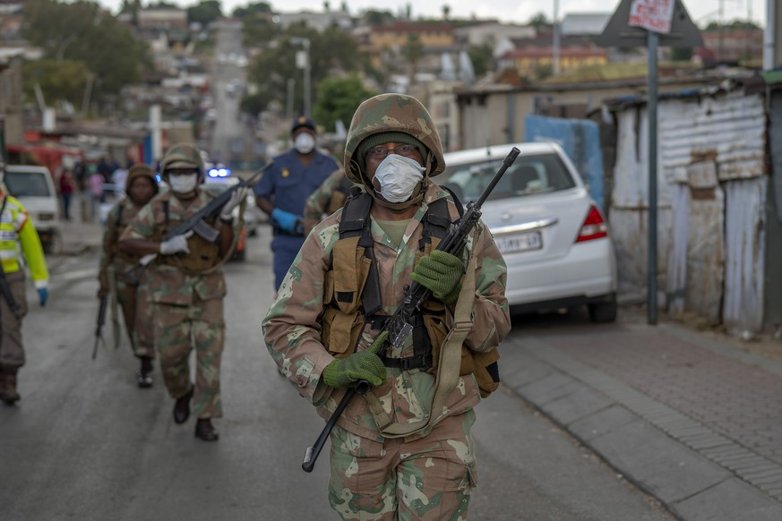 South African National Defense Forces patrol the densely populated Alexandra township east of Johannesburg Friday, March 27, 2020. South Africa went into a nationwide lockdown for 21 days in an effort to mitigate the spread to the coronavirus, but in Alexandra, many people were gathering in the streets disregarding the lockdown. The new coronavirus causes mild or moderate symptoms for most people, but for some, especially older adults and people with existing health problems, it can cause more severe illness or death.(AP Photo/Jerome Delay)