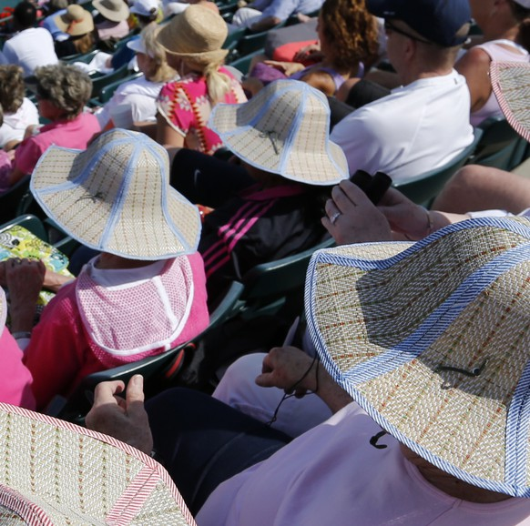 Tennis fans all wear the same style hats to protect them from the sun during the Chanelle Scheepers, of South Africa, and Venus Williams match on Billie Jean Court during the Family Circle Cup tennis tournament in Charleston, S.C., Wednesday, April 2, 2014.  (AP Photo/Mic Smith)