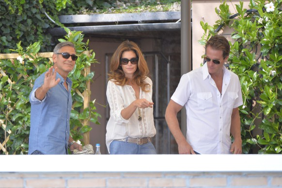 """US actor George Clooney (L), topmodel Cindy Crawford and her husband Rande Gerber (R) leave their table on September 27, 2014 at the Cipriani Hotel in Venice before his wedding with British Amal Alamuddin in Venice. George Clooney has said goodbye to bachelorhood in Venice with a stag party at his favourite restaurant with Hollywood chums, and was gearing up for a day of glamourous pre-wedding celebrations. The actor had swept into the floating city yesterday with his British fiancee Amal Alamuddin on a watertaxi dubbed """"Amore"""", zipping up the Grand Canal to cheers from fans at the start of nuptials set to draw out over the weekend.  AFP PHOTO / ANDREAS SOLARO"""