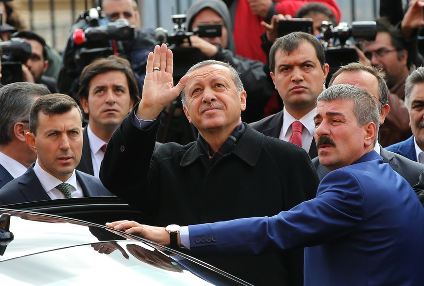 Turkey's President Recep Tayyip Erdogan, center, escorted by his bodyguards waves to his supporters after he casts his vote outside a polling station, in Istanbul, Sunday, Nov. 1, 2015.  Turks headed to the polls Sunday for the second time in five months in what is being seen as a crucial general election that will determine whether the ruling party can restore the parliamentary majority it enjoyed for the past 13-years. (AP Photo/Hussein Malla)