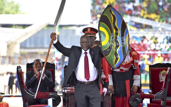 FILE - In this Nov. 5, 2015, file photo, Tanzania's President John Magufuli holds up a ceremonial spear and shield to signify the beginning of his presidency, shortly after swearing an oath during his inauguration ceremony at Uhuru Stadium in Dar es Salaam, Tanzania. As of late May 2020, the country