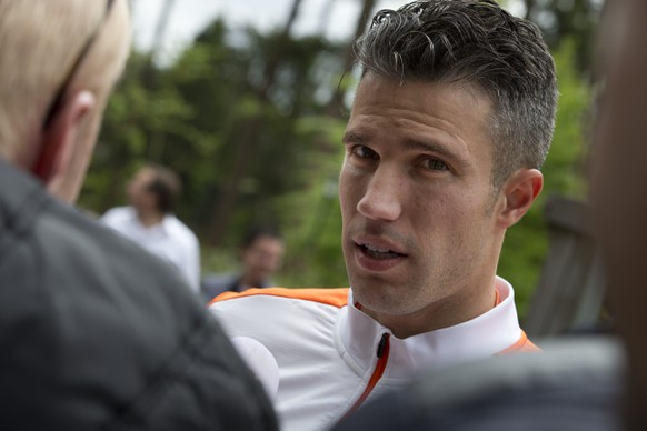 """Manchester United player Robin van Persie, and captain of the Dutch soccer team, answers questions of reporters after a team training session in Hoenderloo, eastern Netherlands, Thursday, May 15, 2014. Louis van Gaal, the 62-year-old coach of the Dutch soccer team, who is widely expected to be the manager of Manchester United next season, has been experimenting in recent days with a new formation which he says may sound more defensive, but will be executed according to the """"Dutch school"""" of attacking football. (AP Photo/Peter Dejong)"""