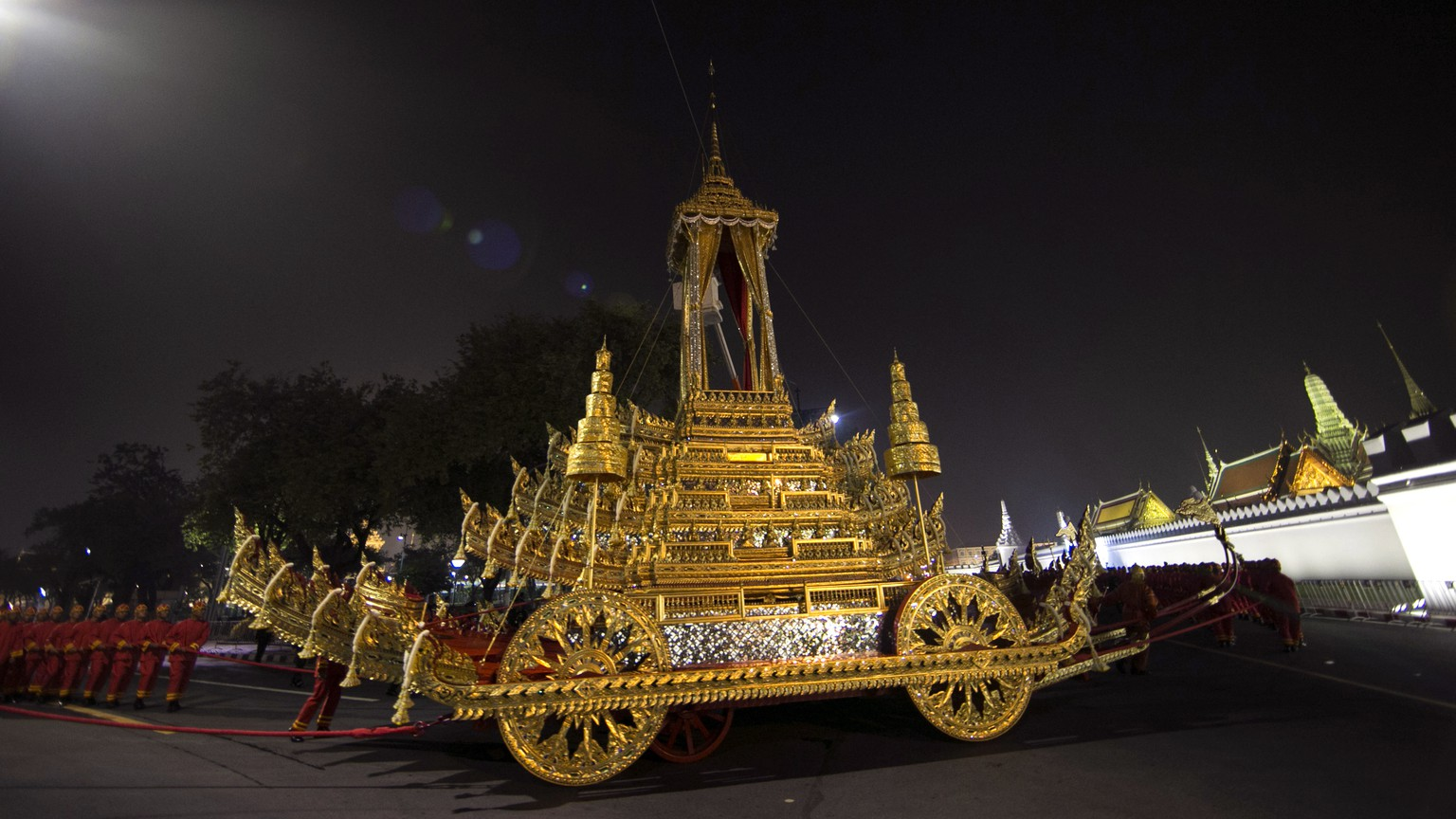 The royal officials pull to the royal chariot which will be used to carry the body and the royal urn of the late Thai King Bhumibol Adulyadej, before royal funeral past the Grand Palace during the Royal Funeral in Bangkok, Thailand, Thursday, Oct. 26, 2017. Thailand on Wednesday began an elaborate five-day funeral for King Bhumibol with his son, the new monarch, performing Buddhist merit-making rites in preparation for moving Bhumibol's remains to a spectacular golden crematorium.(AP Photo/Wason Wanichakorn)