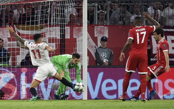 Bayern goalkeeper Sven Ulreich, makes a save ahead of Sevilla's Carlos Joaquin Correa during the Champions League quarter final second leg soccer match between FC Bayern Munich and Sevilla FC at the Allianz Arena stadium in Munich, Germany, Wednesday, April 11, 2018. (Sven Hoppe/dpa via AP)