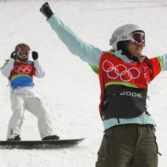 Tanja Frieden of Switzerland reacts after winning a gold medal, as American Lindsey Jacobellis, rear, finishes second after crashing in sight of the finish line in the final of the Women's Snowboard Cross competition at the Turin 2006 Winter Olympic Games in Bardonecchia, Italy, Friday, Feb. 17, 2006. Jacobellis took a silver medal, Dominique Maltais of Canada bronze. (KEYSTONE/AP Photo/Lionel Cironneau)