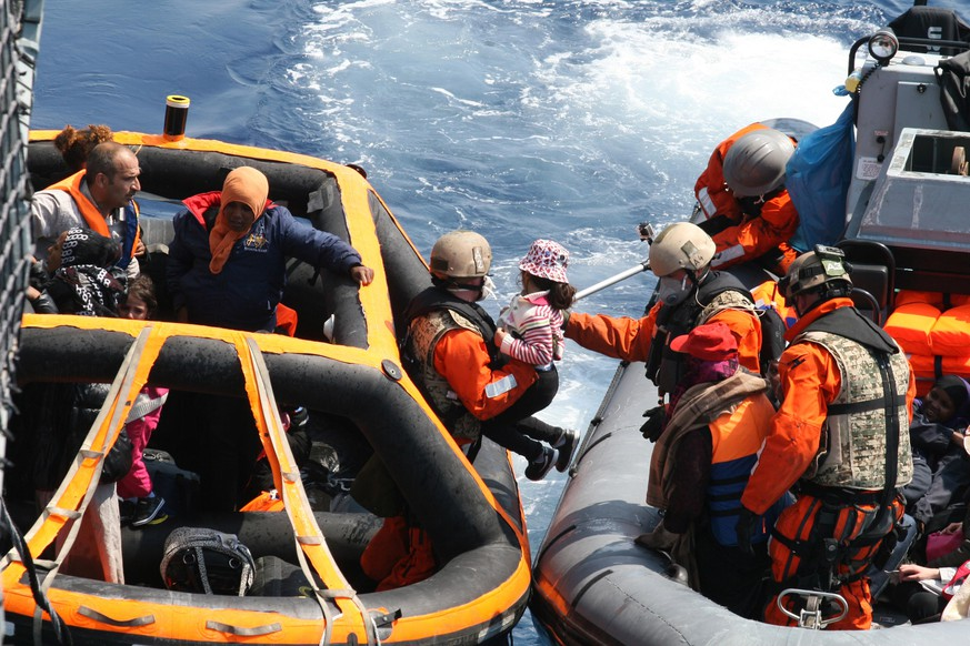 In this Saturday, June 6, 2015 photo provided by German Bundeswehr soldiers of the German frigate 'Hesse' rescue refugees in the Mediterranean Sea. Naval vessels from Italy, Britain, Ireland and other countries steamed toward the waters off Libya on Saturday to rescue the latest wave of migrants from smugglers' boats.  (Bundeswehr Soldaten der Fregatte Hessen retten am 06.06.2015 weitere Schiffbrüchige aus dem Mittelmeer. (Alexander Gottschalk/Bundeswehr via AP)