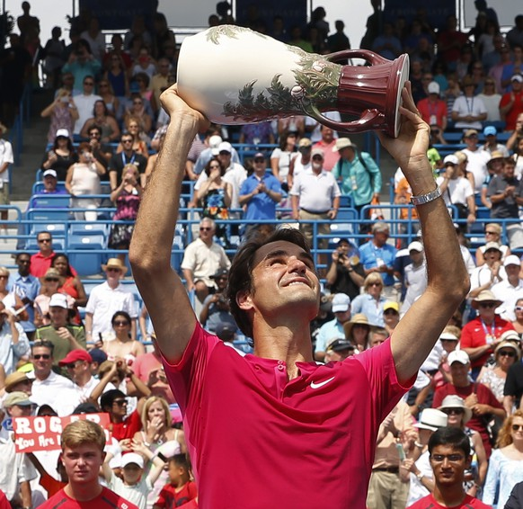 Roger Federer, of Switzerland, holds the Rookwood Cup after winning the men's final against Novak Djokovic, of Serbia, at the Western & Southern Open tennis tournament, Sunday, Aug. 23, 2015, in Mason, Ohio. Federer defeated Djokovic 7-6 (1), 6-3. (AP Photo/John Minchillo)