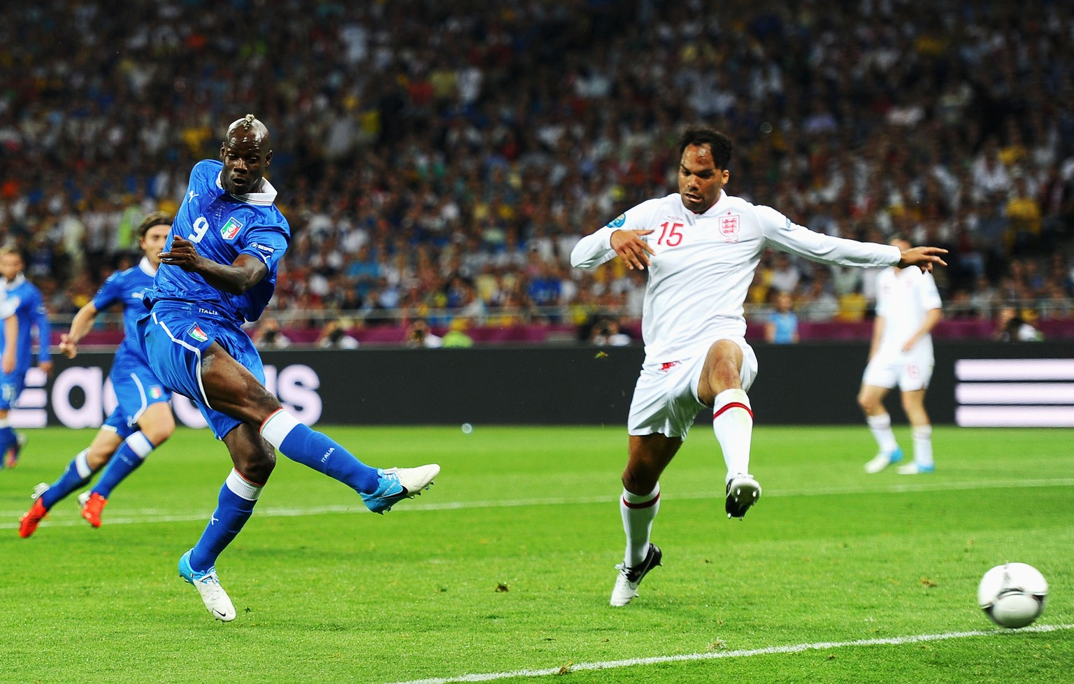KIEV, UKRAINE - JUNE 24: Mario Balotelli of Italy strikes the ball as Joleon Lescott of England runs in during the UEFA EURO 2012 quarter final match between England and Italy at The Olympic Stadium on June 24, 2012 in Kiev, Ukraine.  (Photo by Laurence Griffiths/Getty Images)
