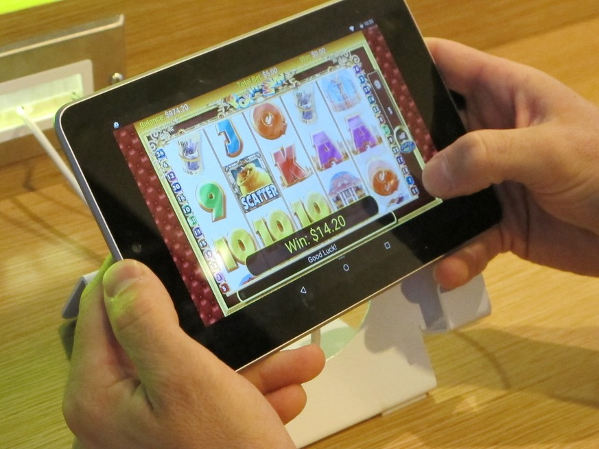In this April 15, 2015 photo, an employee at Resorts Casino Hotel tries a touch-screen tablet device in the Atlantic City, N.J. casino's new Internet gambling lounge. The room is designed to help traditional casino customers sign up for and become more comfortable with Internet gambling. (AP Photo/Wayne Parry)