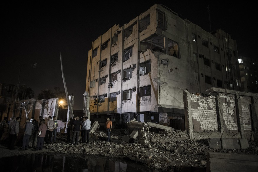 epa04889659 The scene where a bomb detonated next to a national security building in the Shubra neighborhood of Cairo, Egypt, early 20 August 2015. A massive car bomb that hit a security building in the northern suburb of Shubra al-Kheima injured six policemen, according to the Interior Ministry. The bomber parked his car outside the National Security building's security cordon before fleeing on a motorcycle that had been following him.  EPA/OLIVER WEIKEN