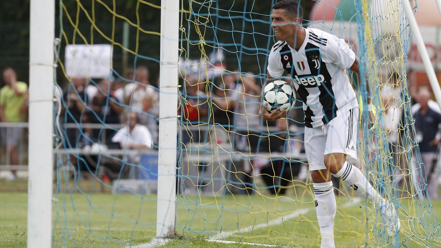 Juventus' Cristiano Ronaldo holds the ball in a goal during a friendly match between the Juventus A and B teams, in Villar Perosa, northern Italy, Sunday, Aug.12, 2018. (AP Photo/Antonio Calanni)