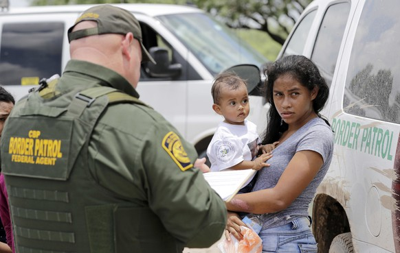 FILE - In this June 25, 2018, file photo, a mother migrating from Honduras holds her 1-year-old child as surrendering to U.S. Border Patrol agents after illegally crossing the border near McAllen, Texas. The women paid a smuggler to get them across the river. Once agents spotted the smuggler, he retreated to Mexico and the women surrendered to officials. Despite calls from some liberal Democrats to eliminate the Immigration and Customs Enforcement, most Democrats show little appetite for abolishing the agency at the center of the drama over immigrant children separated from their parents this summer. (AP Photo/David J. Phillip, File)
