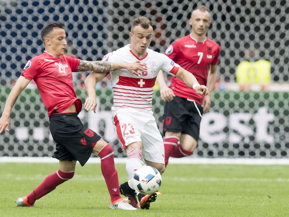 Albania's midfielder Ergys Kace, left, fights for the ball with Swiss forward Xherdan Shaqiri, center, in front of Albania's defender Ansi Agolli, right, during the UEFA EURO 2016 group A preliminary round soccer match between Albania and Switzerland, at the Stadium Bollaert-Delelis, in Lens, France, Saturday, June 11, 2016. (KEYSTONE/Jean-Christophe Bott)